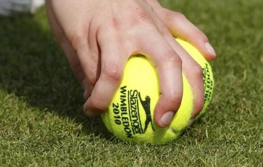 A ball boy picks up tennis balls during the match between Andrea Hlavackova of the Czech Republic and Thailand's Noppawan Lertcheewakam at the 2010 Wimbledon Tennis Championships in London